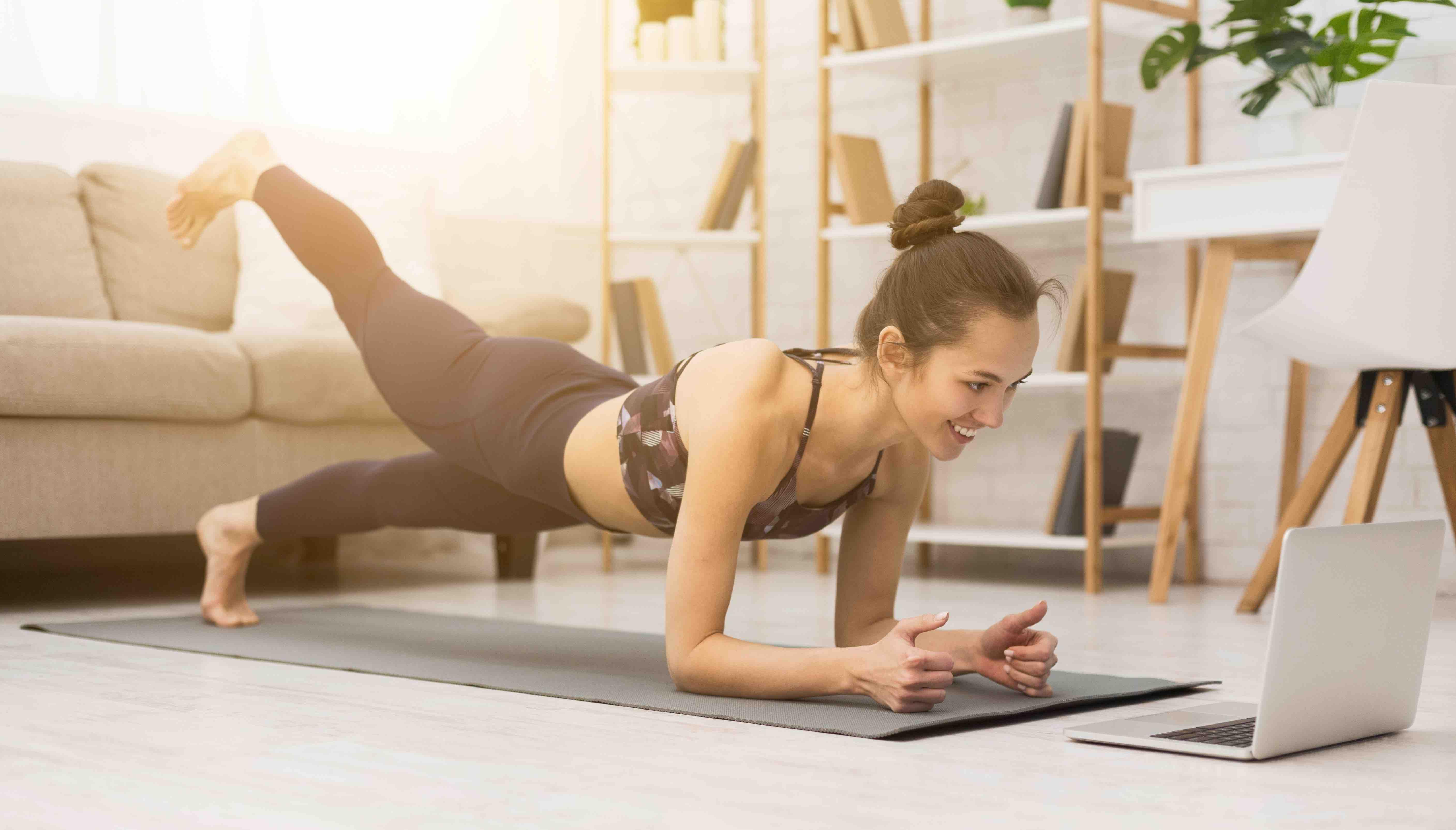 Mulher treinando em casa assistindo vídeos no laptop