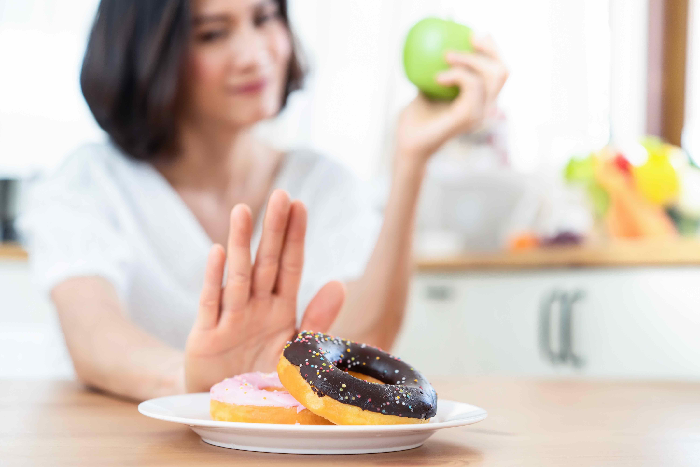 Jovem mulher evitando o consumo de comida com açúcar, pouco saudável