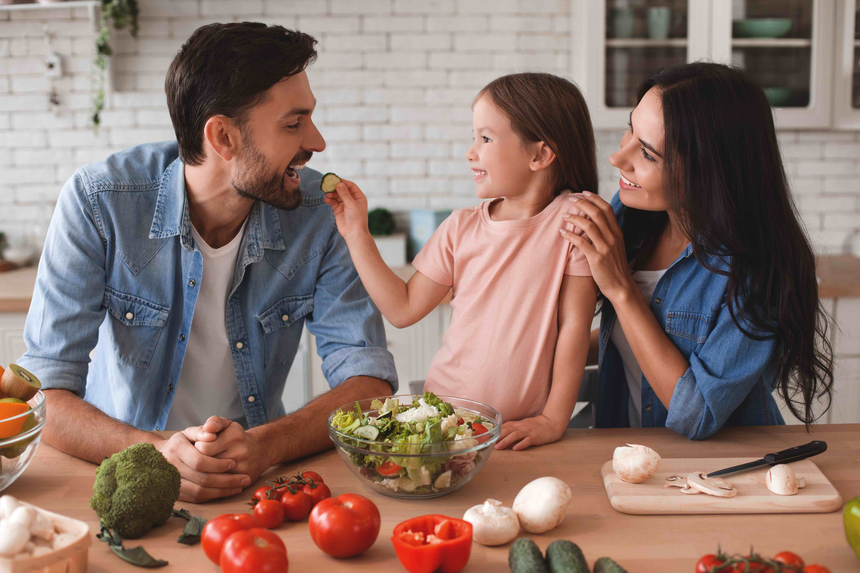 família preparando salada para o almoço, filha, alimentando o pai com uma fatia de pepino na cozinha