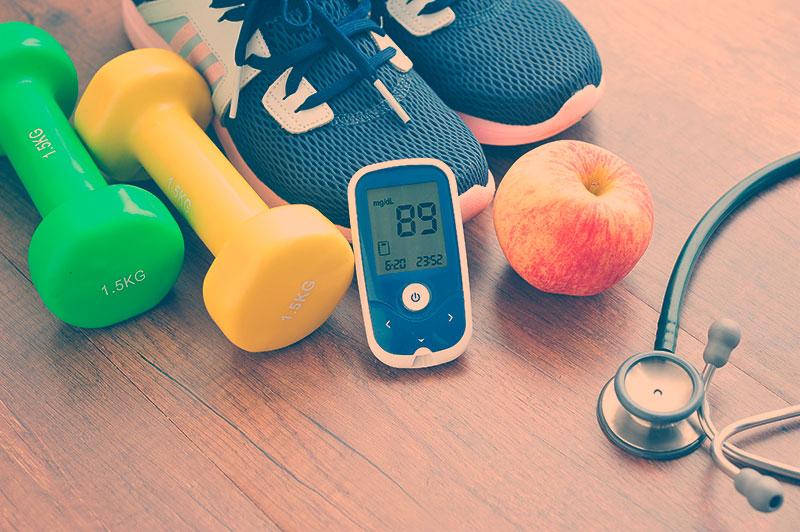 Pesos, tênis de corrida, maçã estetoscópio e medidor de glicose colocados no chão. Imagem representando a ideia do que fazer com diabetes no isolamento social.