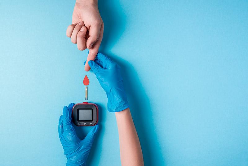 Enfermeiro de luvas azuis, segurando o dedo de uma paciente, com aparelho para medição de diabetes e ilustração de gota de sangue, sobre fundo azul.