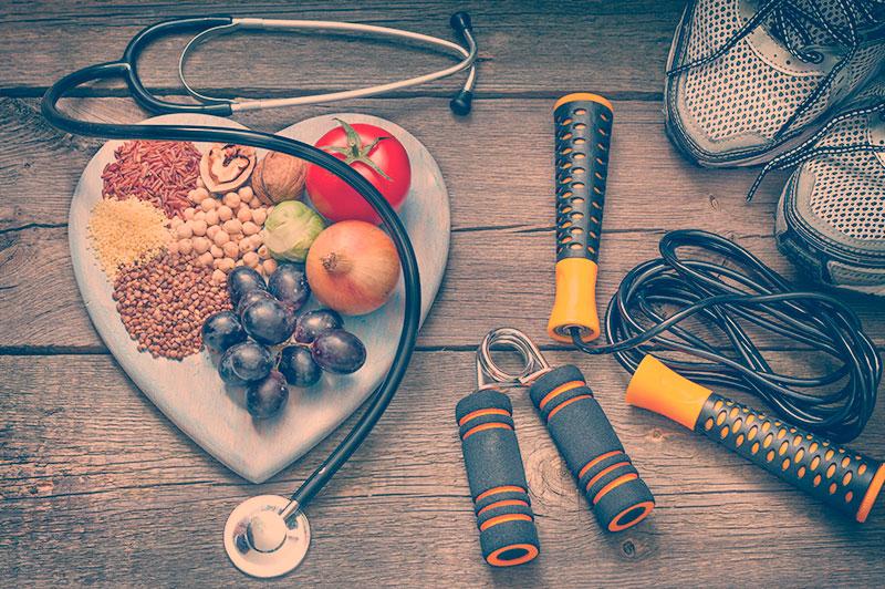 Medicina do estilo de vida, comida saudável, acessórios para exercícios e um estetoscópio.