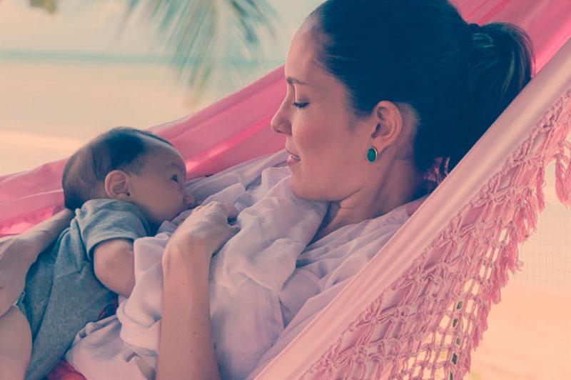 Dra. Ana Luiza Cardoso amamentado sua filha em uma rede, na praia. Aleitamento materno e amamentação