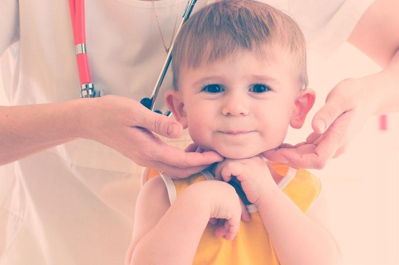 Médica endocrinologista examinando tireóide de criança pequena em consltório. Hipotireoidismo na infância.