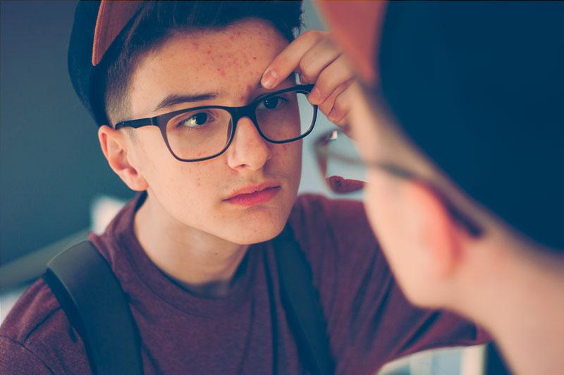 Puberdade Precoce - Imagem de menino criança olhando no espelho, de óculos, com muitas espinhas no rosto.