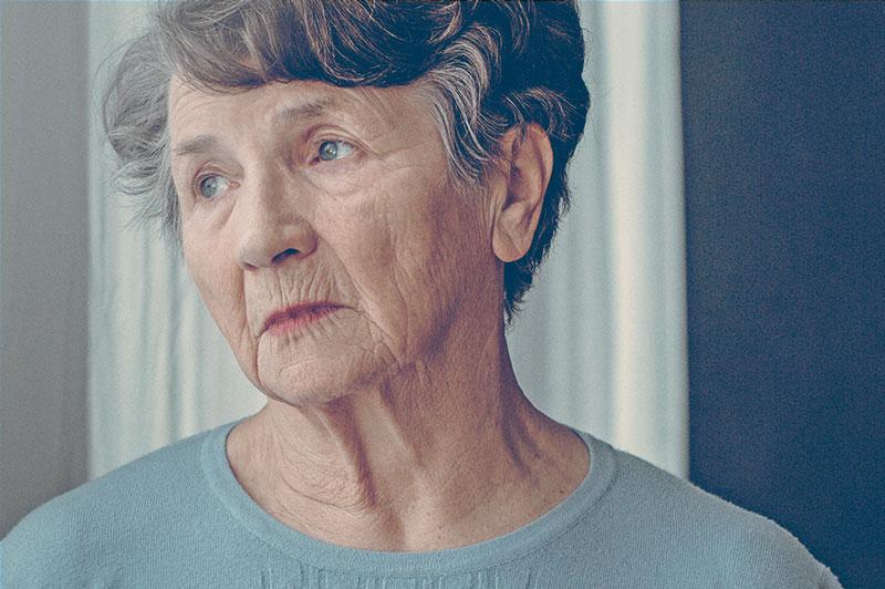 Senhora olhando para o nada, simbolizando alguém com Doença de Alzheimer