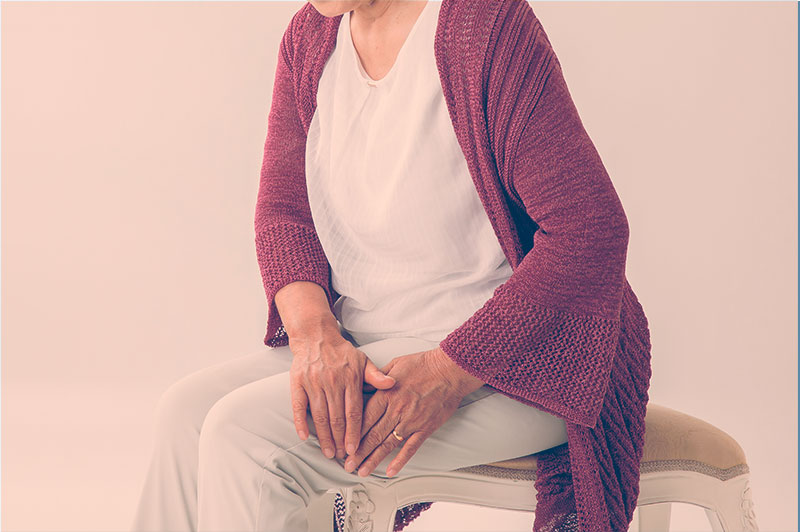 Imagem de uma senhora com algum incômod na perna, representado a ideia de que ela tem osteoporose.