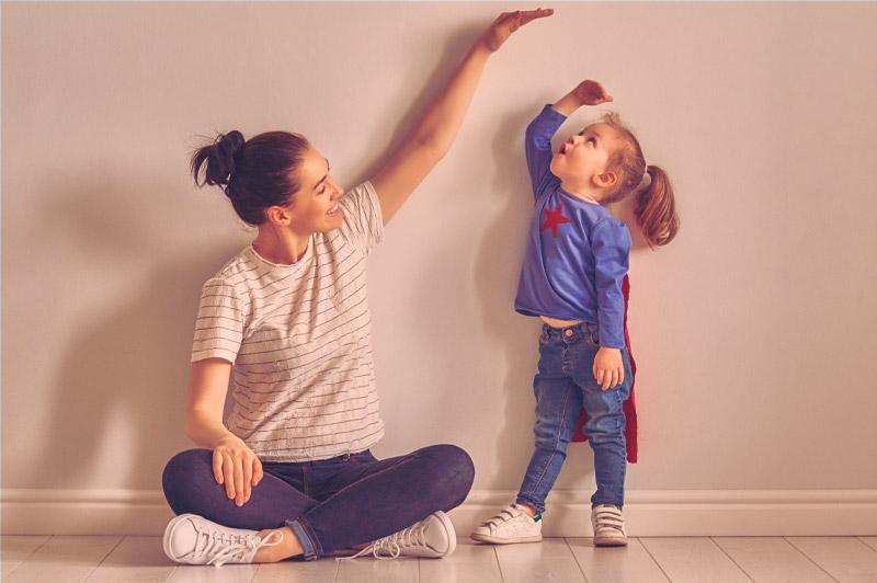 Mãe sentada no chão brincando de medir a filha, encostada na parede, vestida de super-heroina, para ilustrar o crescimento infantil.