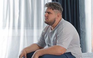 Homem com sobrepeso, sentado na cama pensativo, conceito de relação entra obesidade e testosterona.