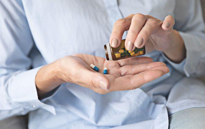 Homem colocando pílulas em sua mão para tomar como automedicação