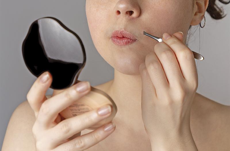 Close no rosto de uma mulher pinçando excesso de pelos no buço com uma pinça e um espelho